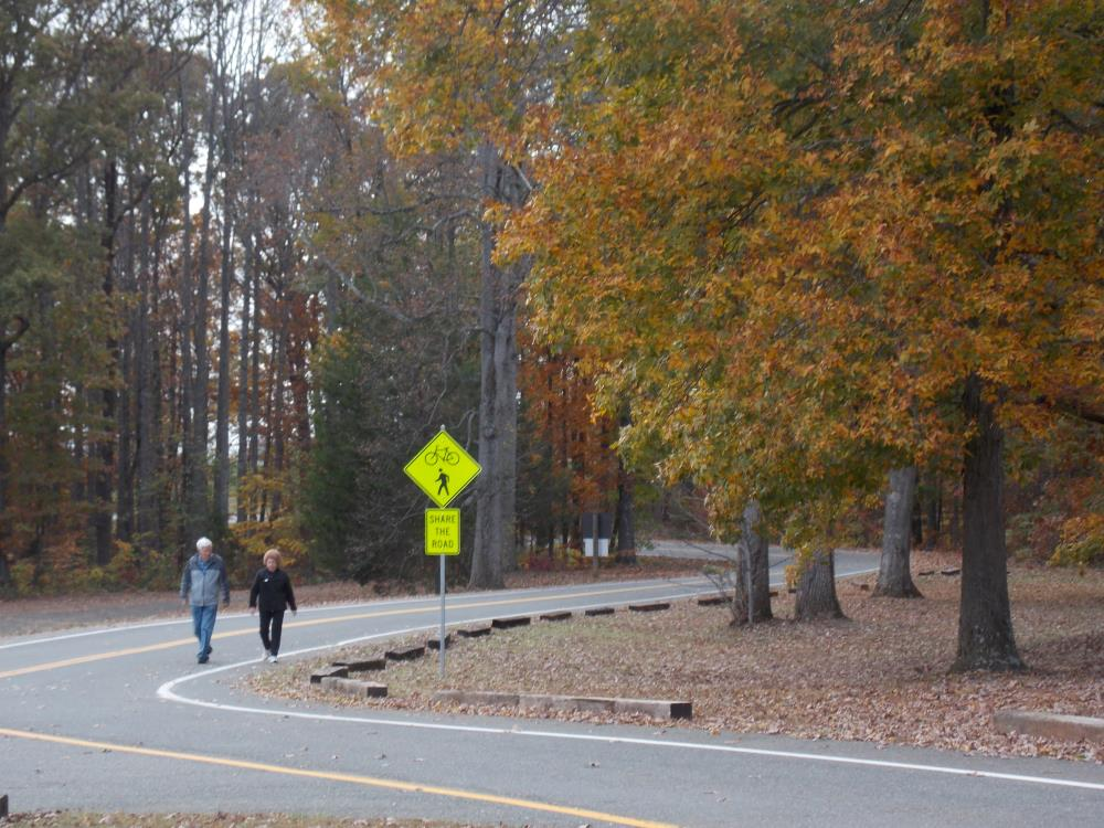 Photo of a man and woman walking along road in Appomattox Community Park on a brisk Fall day