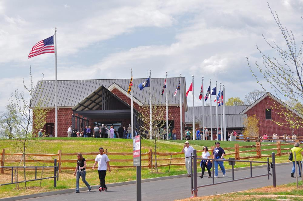 Photo of exterior of American Civil War Museum with people visiting and flags waving in the breeze